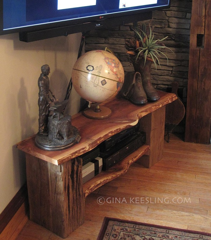 The finished Emergency Media Stand. You can see the alien face's left eye directly in front of the globe. The cowboy boots planter covers the big crack that probably caused the plank to be rejected in the first place. The beam Rob chose for the left side had been exposed to weather for years; it's majorly distressed, almost like animals had scratched or rubbed on it. Perfect.